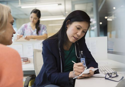Doctor writing prescription for patient in clinic office