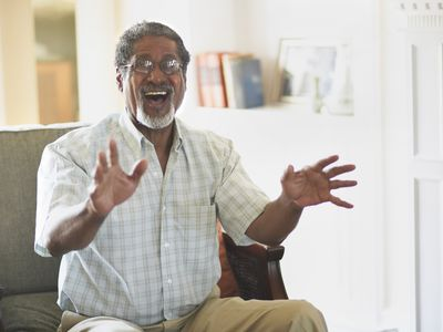 older man smiling and using his hands while telling a story