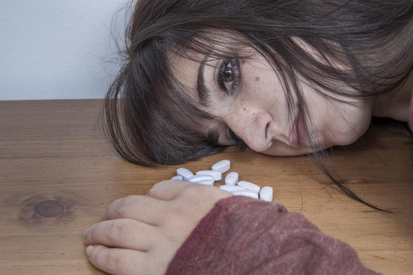 Woman with pile of pills