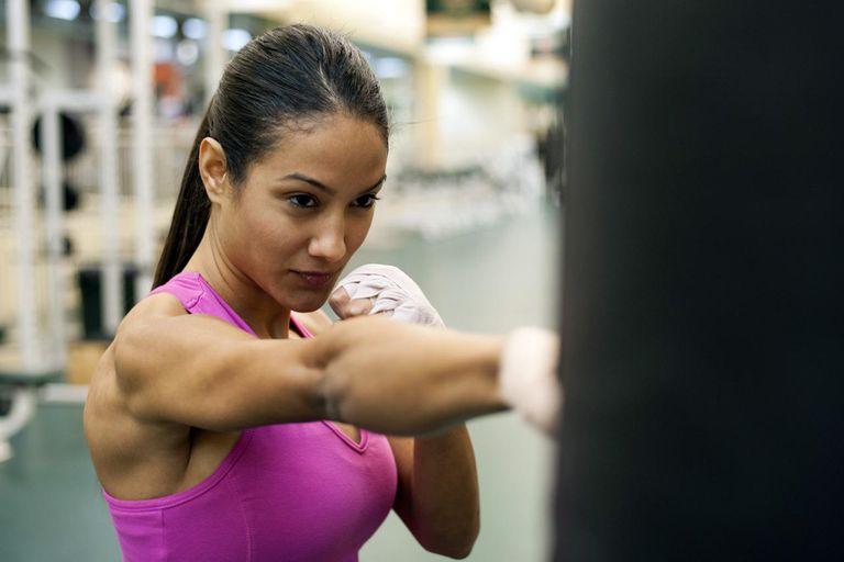 Young woman punching heavy bag