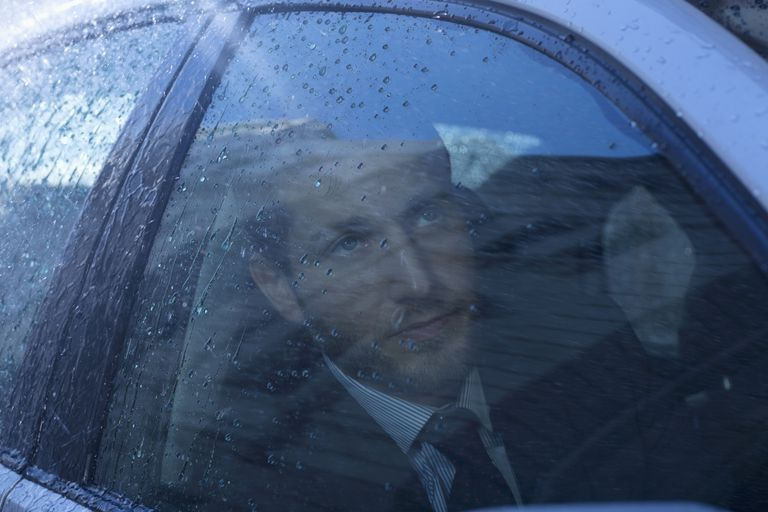 Man looking out rain covered car window