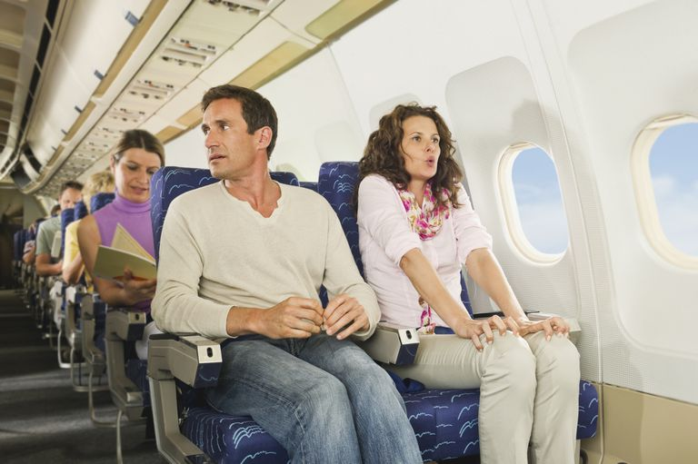 Man and woman looking frightened, sitting in airplane seats