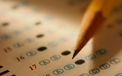 close-up of pencil marking bubbles of multiple-choice exam sheet