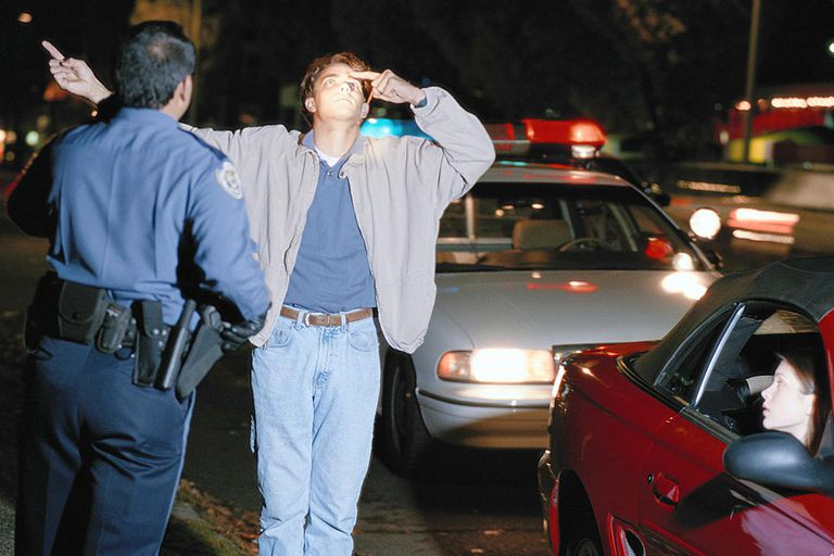 Sobriety Test of a man by a police officer at night