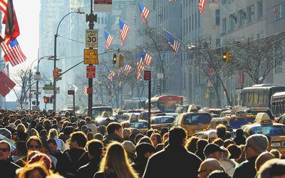 Crowd of people walking down a city sidewalk
