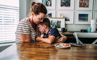 mom hugging sad young boy at dinner table