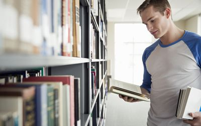 Male student choosing books in college library