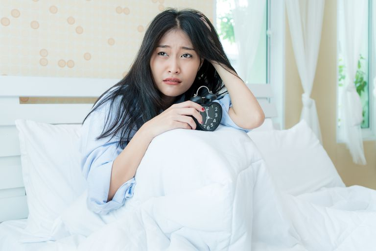 Asian woman holding her alarm clock while underneath her blanket in bed. Asian woman lazy wake up to work in morning Monday.