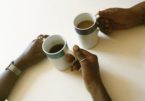 People holding coffee mugs across a table
