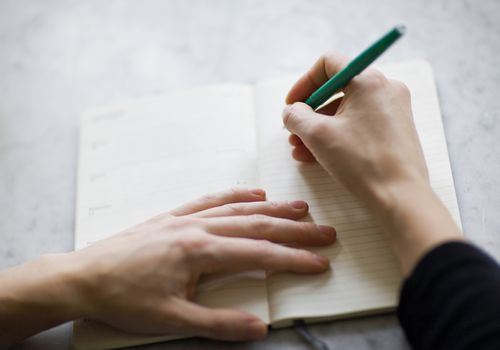 Woman's hand writing in a diary