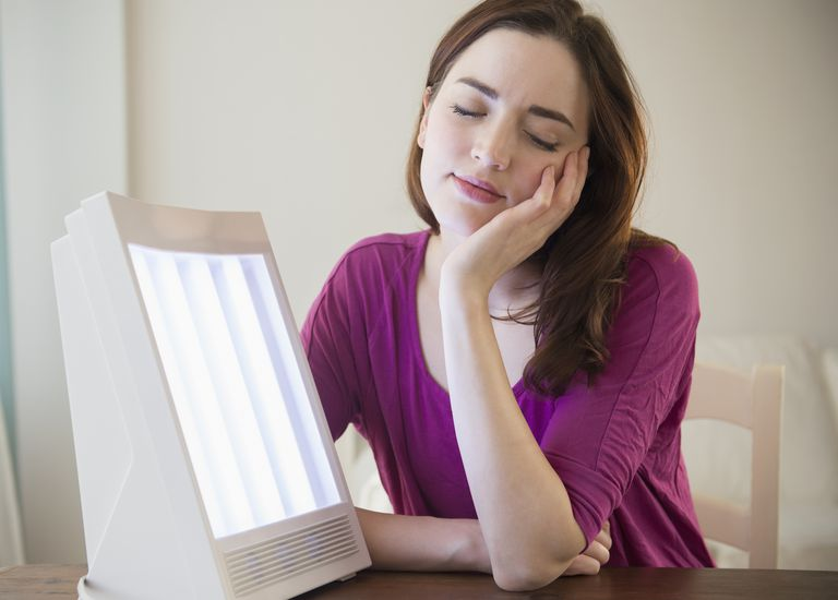 Woman sitting by light therapy box