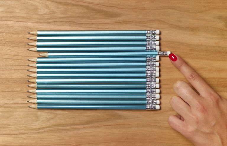 woman's finger lining up a row of pencils on tabletop