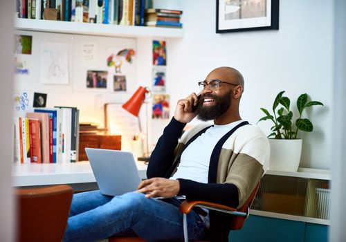 Man sitting in chair smiling while on the phone