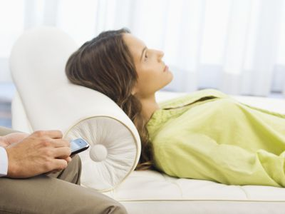 Psychiatrist holding a mobile phone with a patient lying on the bed