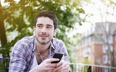 a young man smiling outside while listening to music