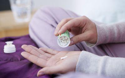 Woman dumping pill into hand
