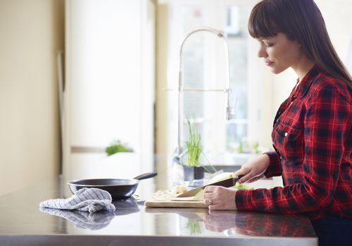 woman cutting onion on kitchen counter