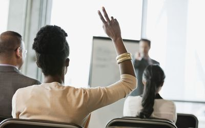 Businesswoman asking question at presentation in office building