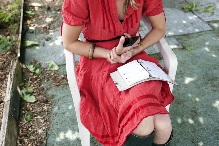 Woman sitting outside looking at her day planner