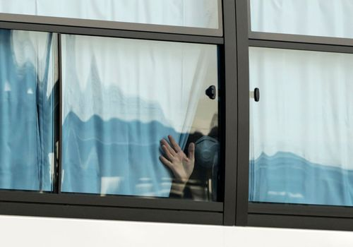 Person looking out window during quarantine