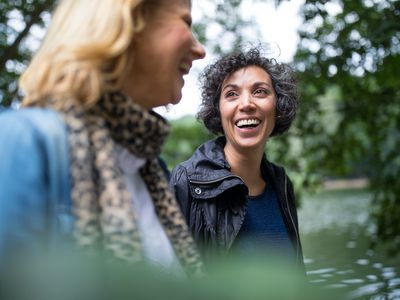 Happy mature woman looking at friend in forest