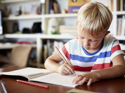 Young boy writing in workbook