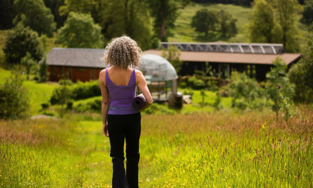 Rear view of mature woman carrying yoga mat walking in eco lodge field