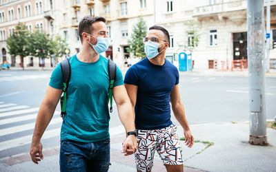 two gay men walking with masks on