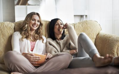 female friends watching movie on couch eating snacks