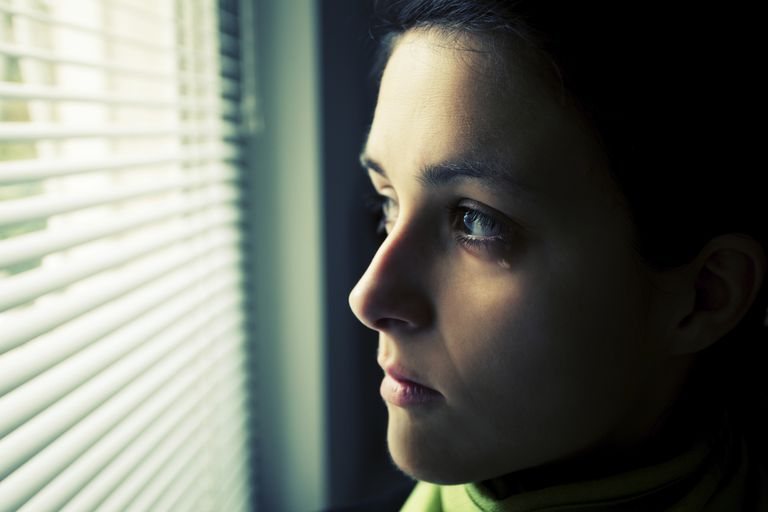 Woman cries while staring out a window