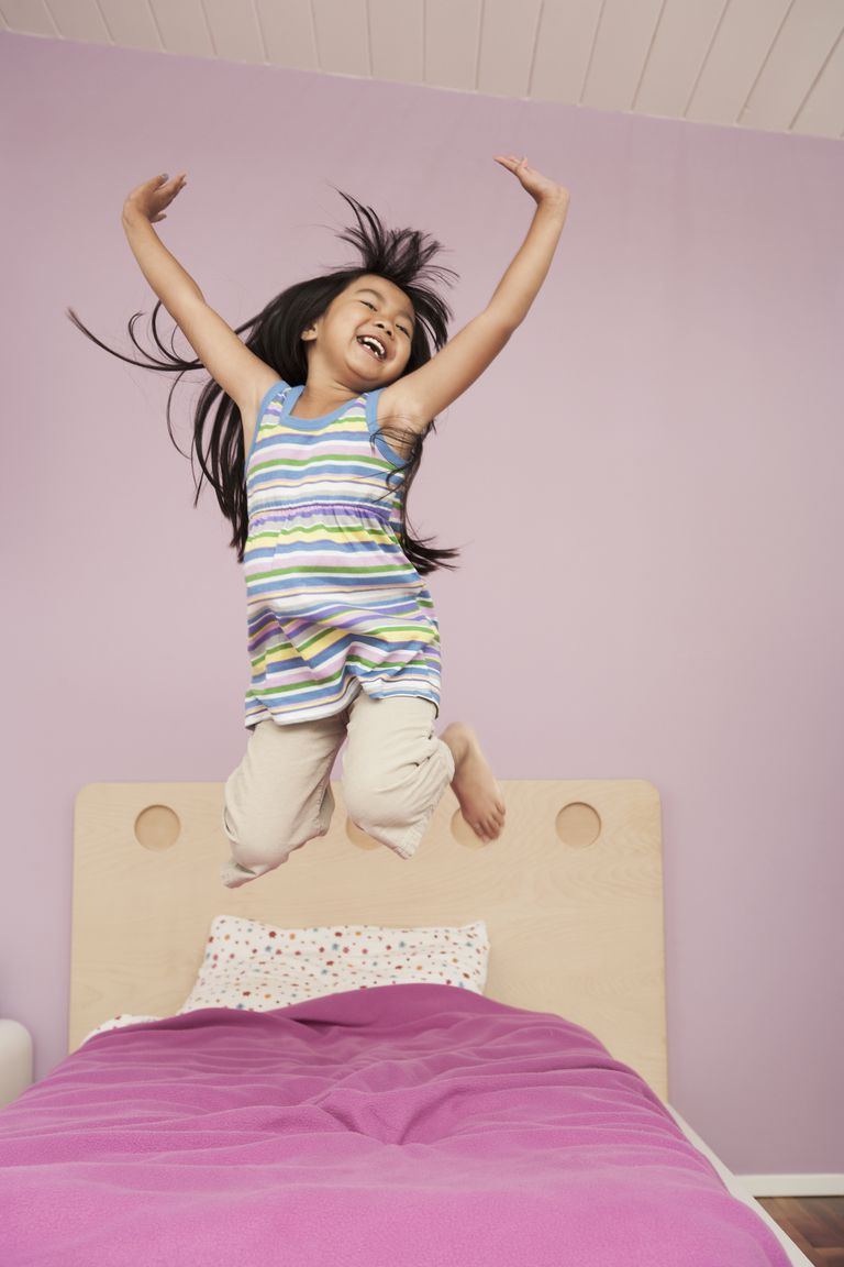 Chinese girl jumping on bed
