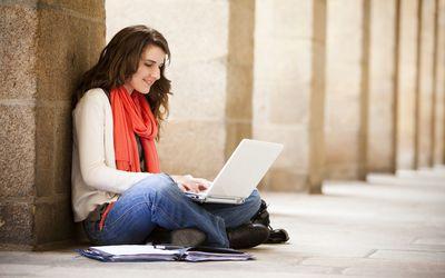 student using laptop in hallway