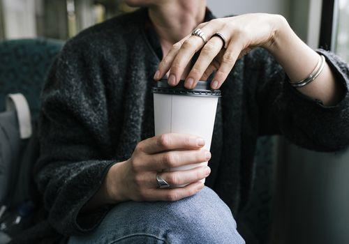 woman holding a paper coffee mug