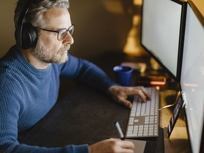 man wearing glasses working at a computer