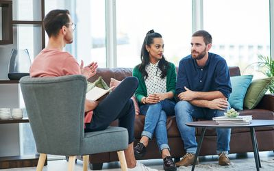 Shot of two young men and a woman having a discussion in a modern office