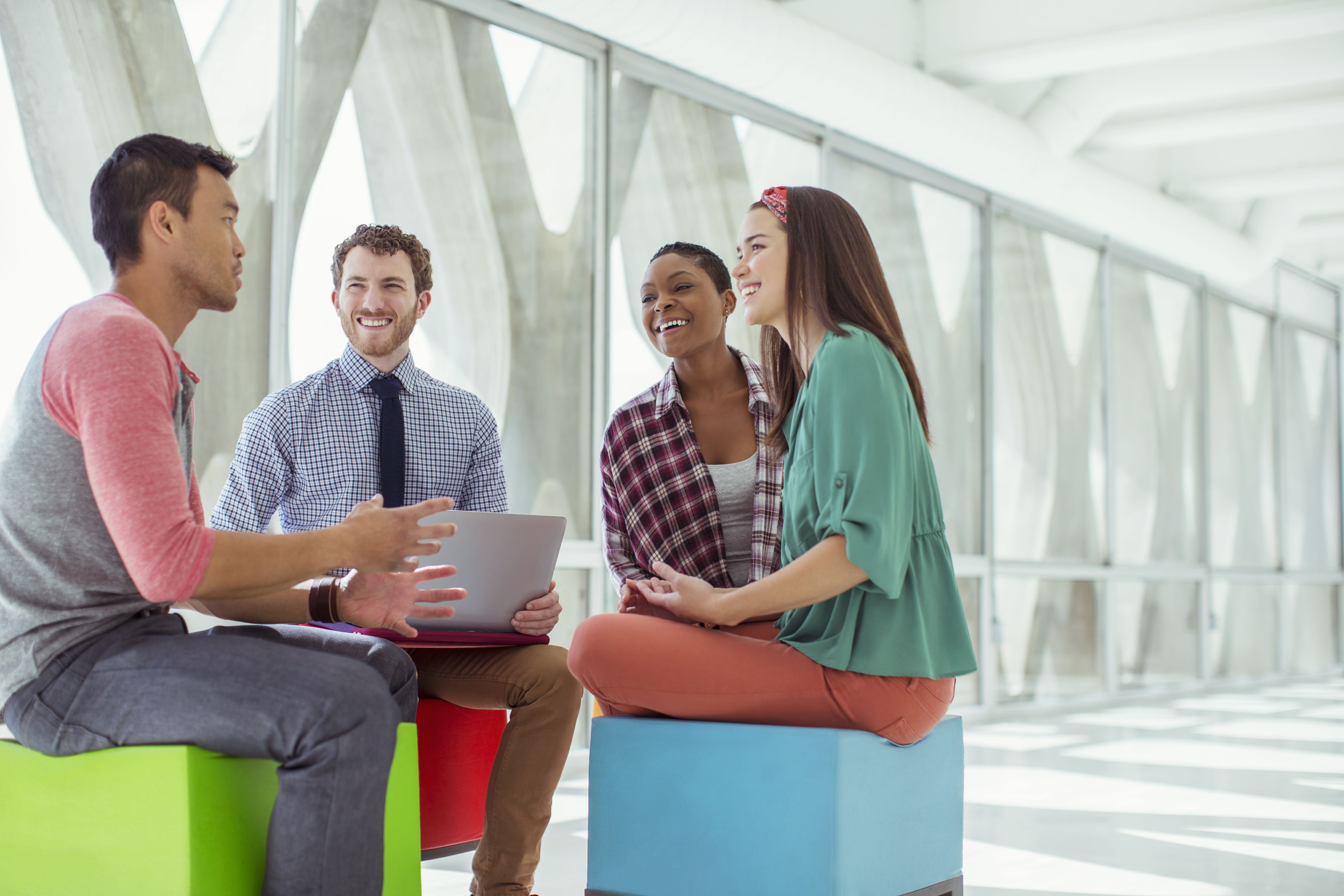Four business people meeting on colorful stools