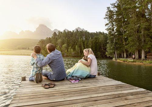 Family sitting at lake suring sunset