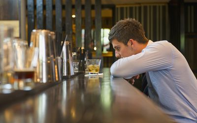Young Man Drinking At Bar Alone