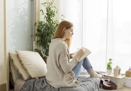 Woman with red hair writing in a journal on the bed.