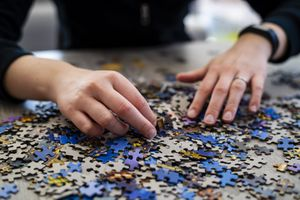 person's hands working on a puzzle