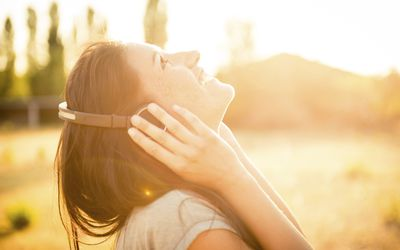 happy young woman listening to music on headphones outdoors