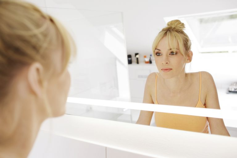 Blonde woman looking confidently at her reflection in the mirror