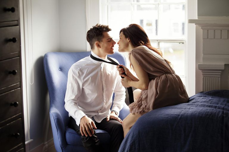 young woman seductively grabbing young man's tie while she sits on the edge of a bed