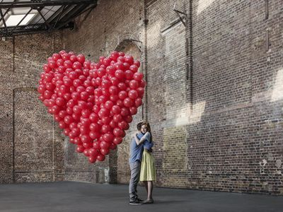 man and woman hugging in a warehouse with a group of red balloons shaped like a heart