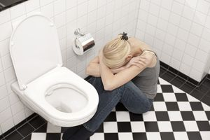 Woman on the floor sits by toilet