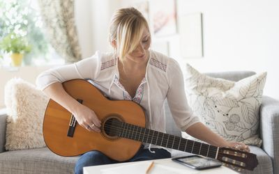 USA, New Jersey, Woman sitting on sofa and playing acoustic guitar