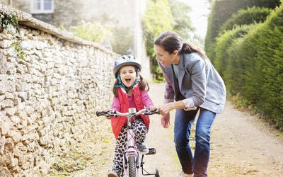 Woman helping young girl learn how to ride bicycle.