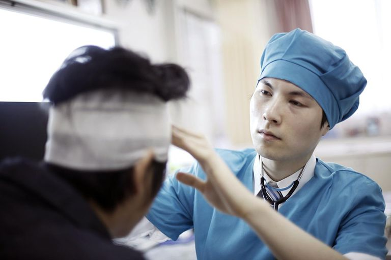 Doctor examining patient with bandaged head