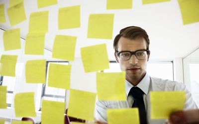Man with many post it notes on a board