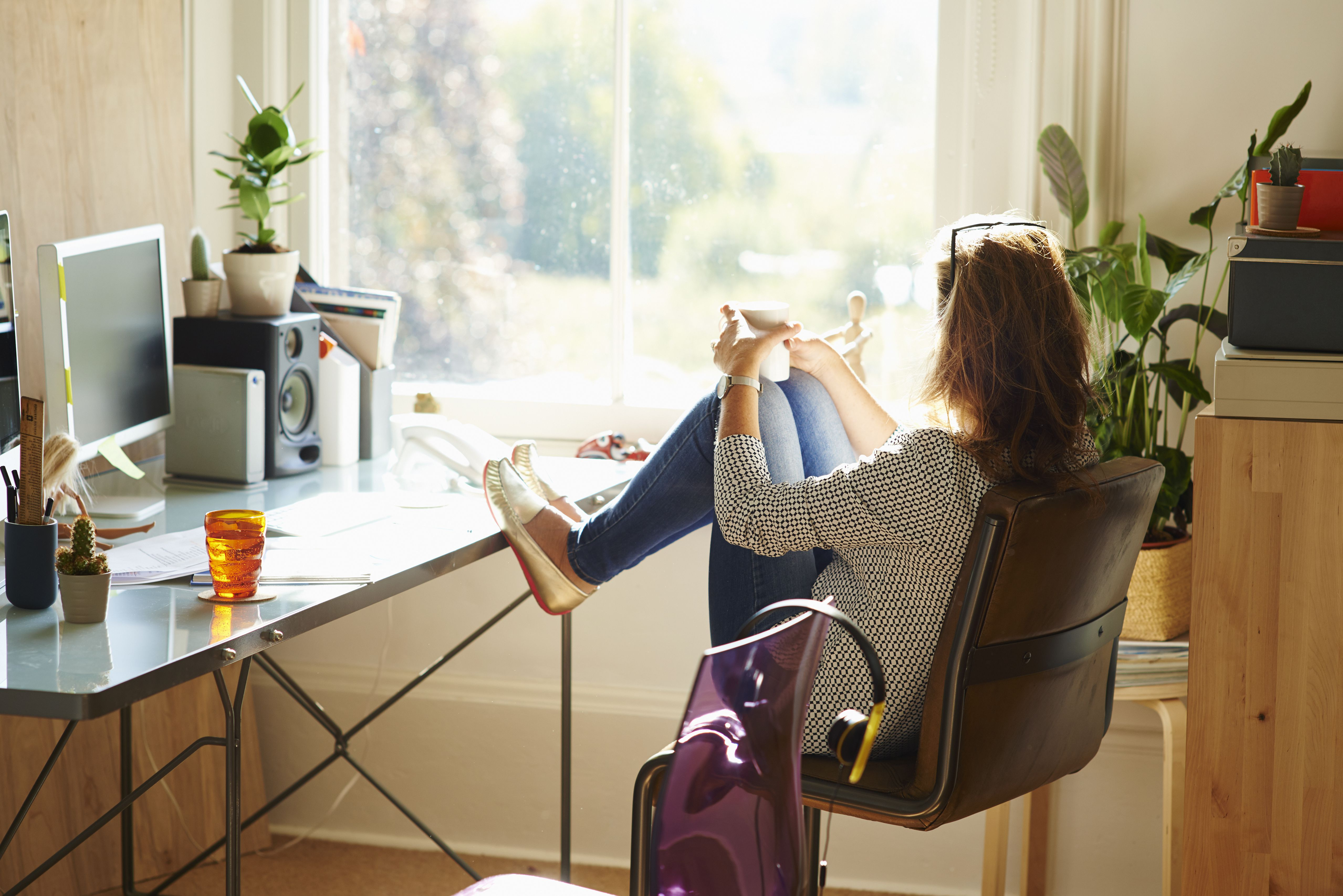 Woman taking a coffee break with her feet up on desk